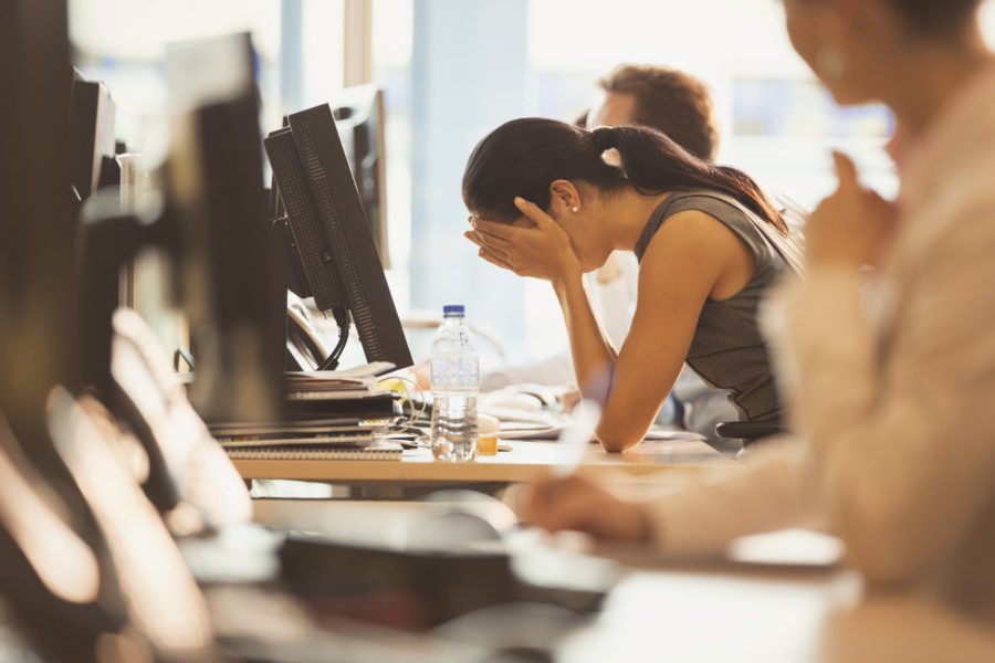 Image of stressed businesswoman with head in hands at office desk