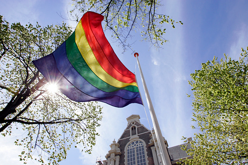 Rainbow flag flies in the mast at Homomonument in front of the Wester Church in Amsterdam, Netherlands.