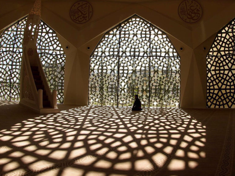Image of man praying in mosque