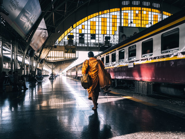 Image of a monk walks through Bangkok's old train station to catch his departure.