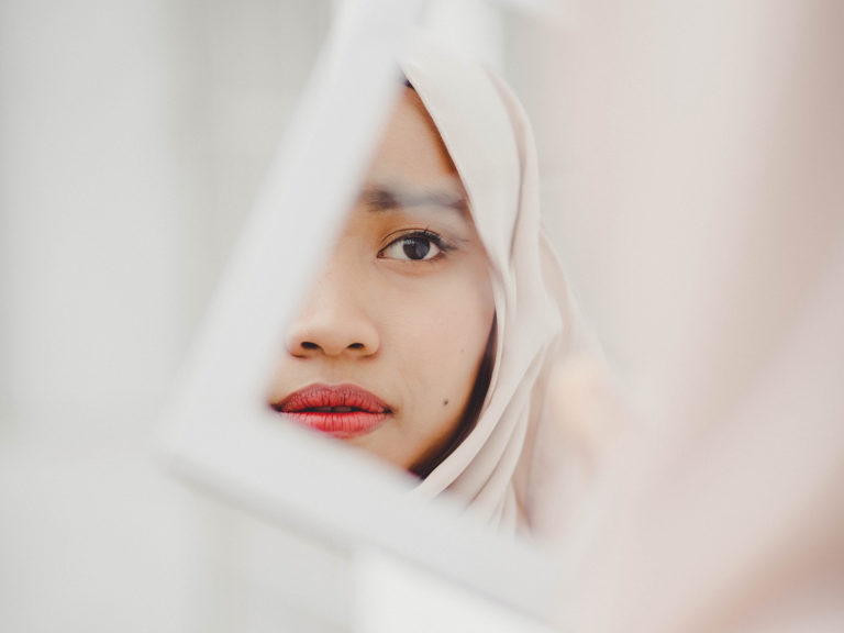Image of muslim woman through a mirror