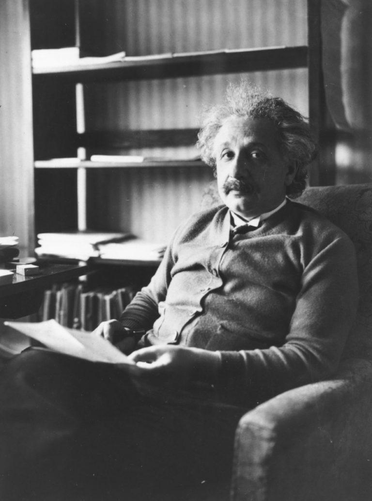 Portrait of physicist Albert Einstein sitting in an armchair and reading, 1929.