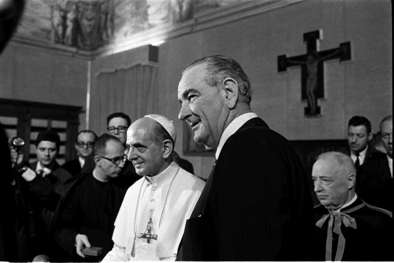 Pope Paul VI and Pres. Lyndon B. Johnson pose for photos at the Vatican as others look on.