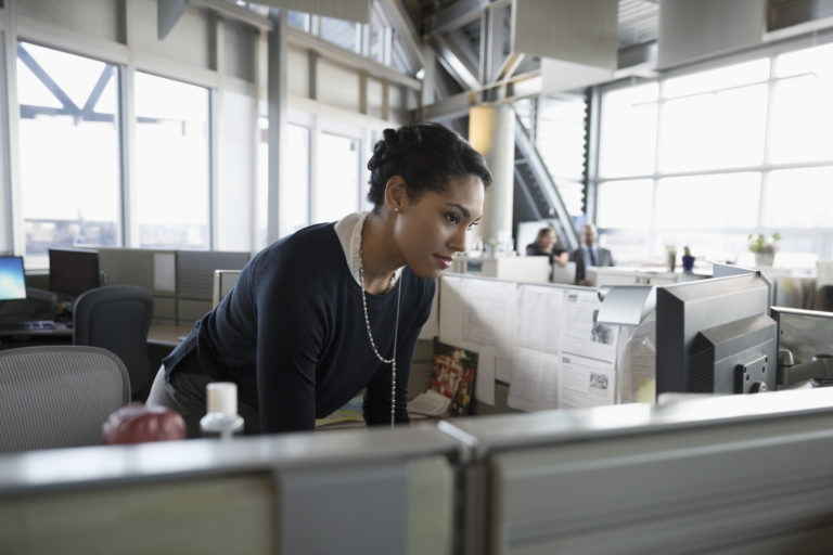 Image of businesswoman using computer in office cubicle
