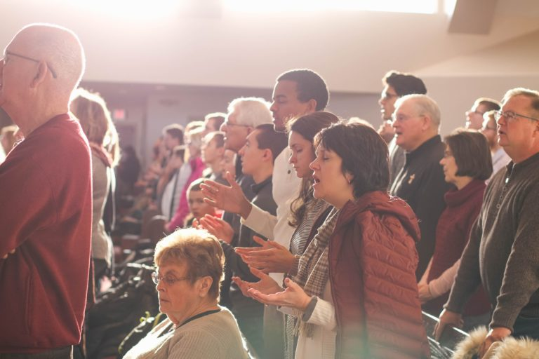 People gather to worship together in sunlit church.