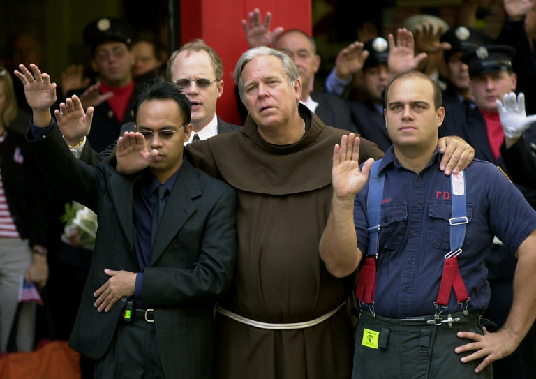 Image of Father Christopher Keenan participating in the funeral for New York Fire Department chaplain Rev. Mychal Judge outside St. Francis of Assisi Church on September 15, 2001