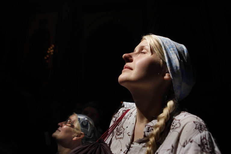 Image of Christian Orthodox worshippers hold their heads up as a ray of light
