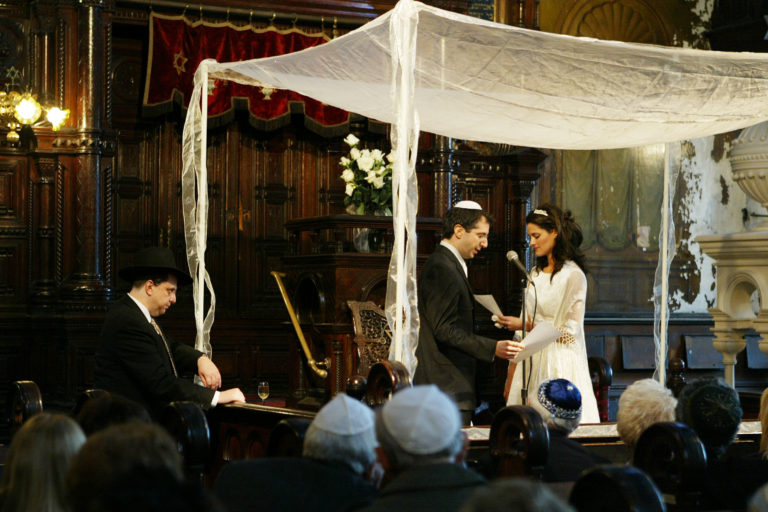 A couple gets married in the Eldridge Street Synagogue in New York City under a chuppah, or wedding canopy, which is used in all Orthodox and Conservative, and in some Reform, ceremonies. The chuppah suggests a royal canopy in which the couple are king and queen that day.