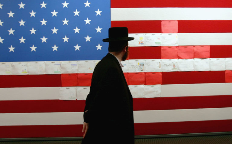 A Jewish man looks at an American flag that was part of a multimedia exhibit in
