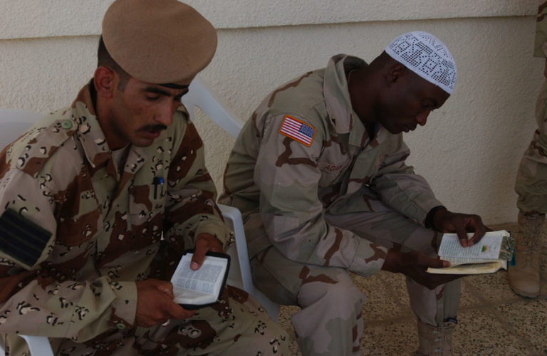 A soldier in the Iraqi Army and a soldier in the U.S. Army read their prayer books during the opening ceremony of the Masjid Al-Mu Mineen or Mosque of The Believers at Camp Cooke in Taji, Iraq.