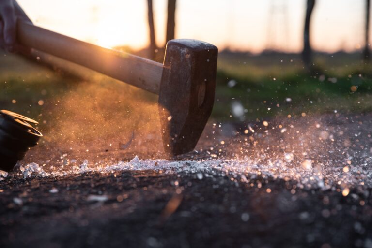 A hammer pounds down into a piece of wood with shattered ice flying.