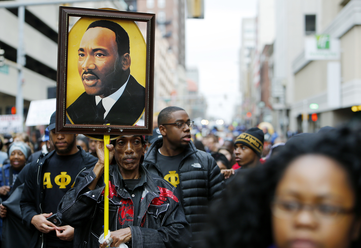Osie James carries a photo of Dr. Martin Luther King Jr. during the annual Martin Luther King Day march on January 16, 2017 in Memphis, Tennessee.