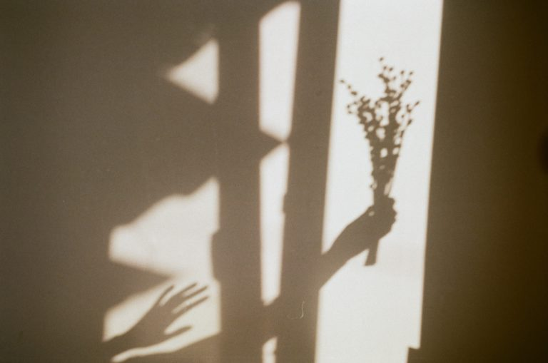 Shadow of someone holding a bouquet of flowers