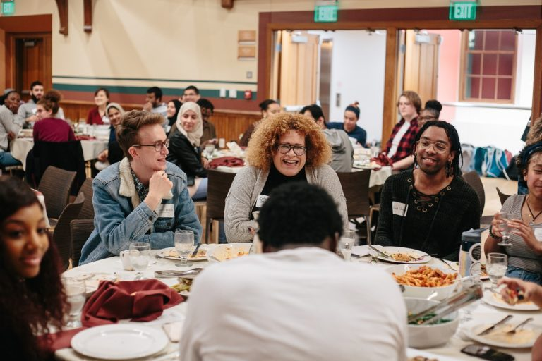A group of People's Supper participants gathered at a table in conversation.