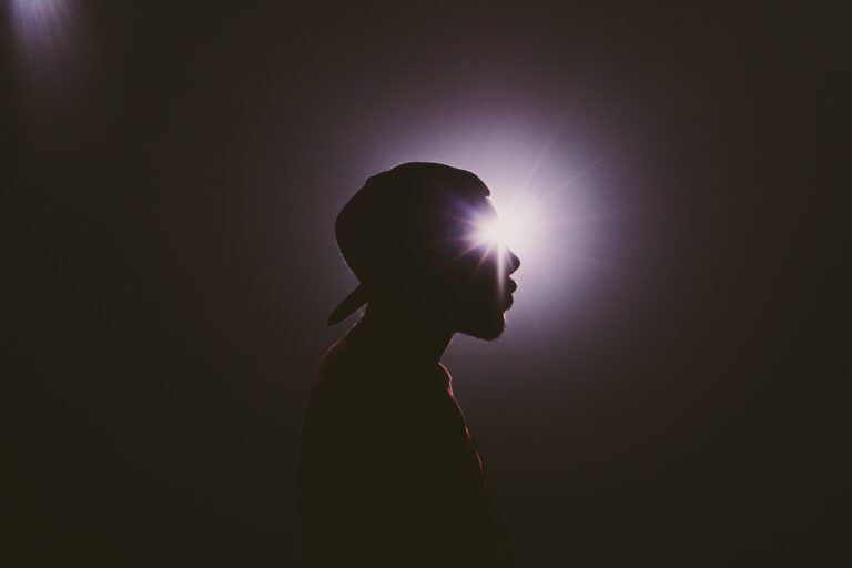 A man's silhouette is illuminated by a sunburst of light.