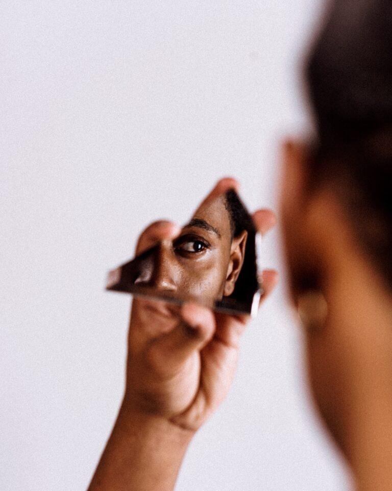 Black man stares into a broken piece of mirror at their reflection.