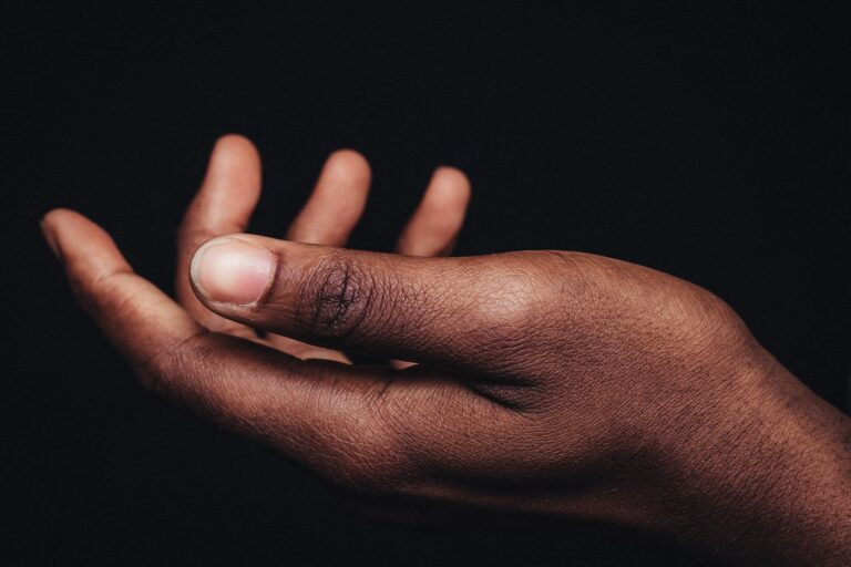 A Black person's hand uncurls toward the sky on a black background.